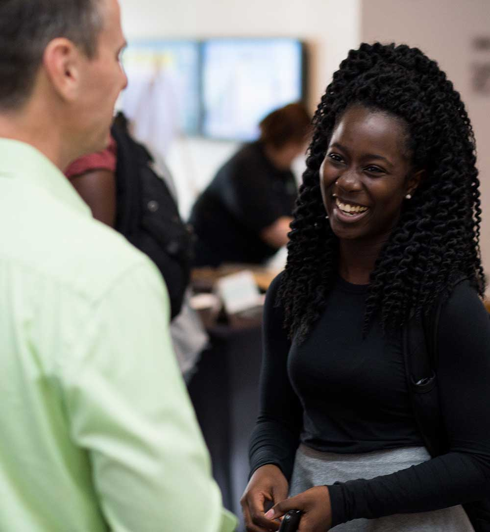 Bloch student smiles while talking with a recruiter from H & R Bloch on campus